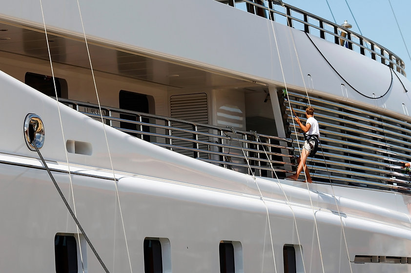 Luxury yacht moored on harbor, being cle