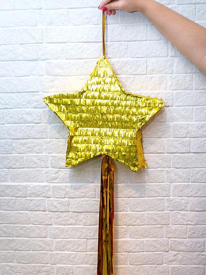Pinhata de estrela dourada com fitas douradas.