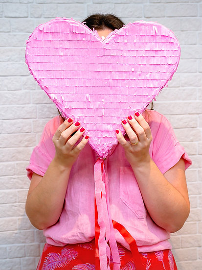 Pinhata de coração rosa com fitas de papel rosa e vermelho.