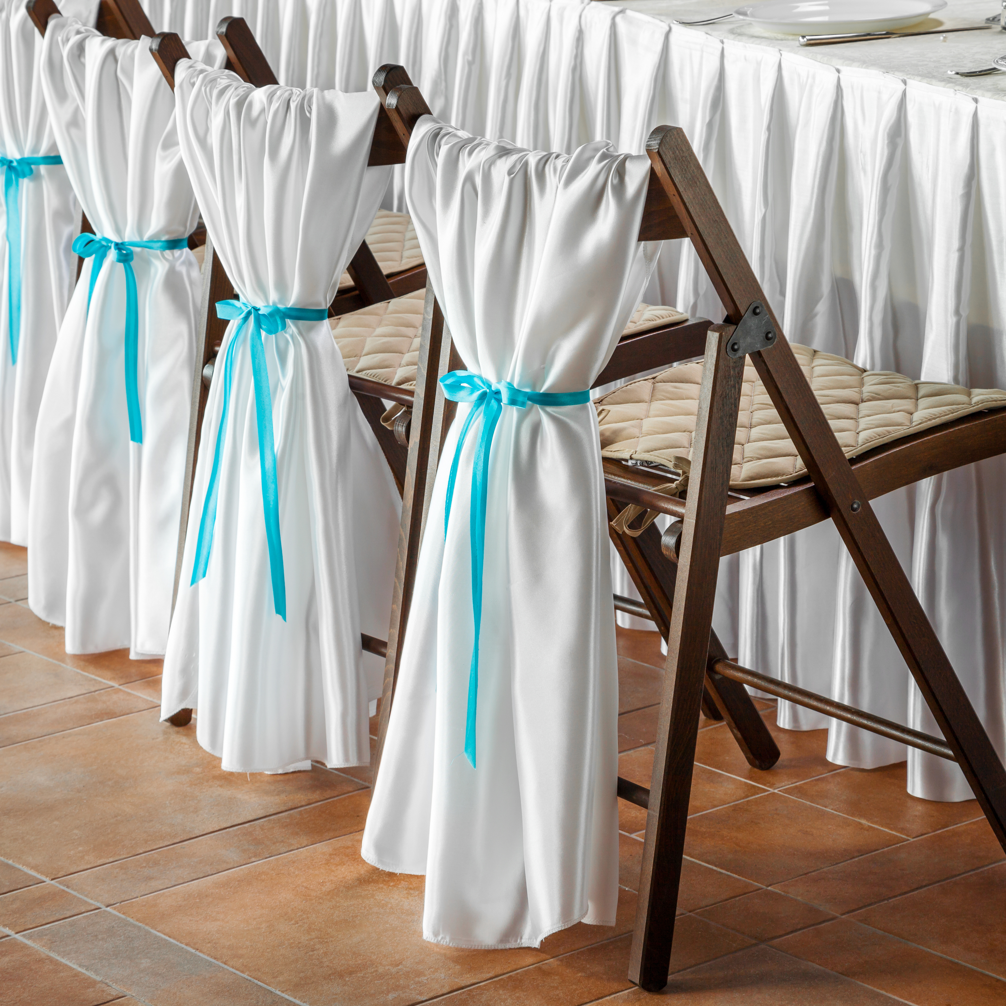 Row Of Wedding Chairs, Decorated With White Fabric And Blue Ribbons.