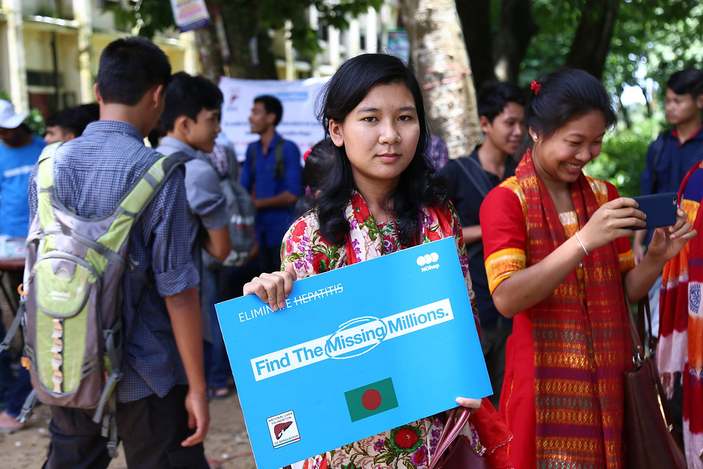 "Featured Image: A ""Chakma"" student holding a ""Find the Missing Millions"" board to support the initiative. The Chakma tribe is the largest indigenous tribe in Bangladesh. They live in Rangamati, Chittagong hills which is in the South-East Bangladesh. A ""Find the Missing Millions"" free hepatitis B and C screening and awareness program organized by the National Liver Foundation of Bangladesh among the people of the Chakma tribe at Rangamati. Courtesy of Zunaid Murshed Paiker, National Liver Foundation of Bangladesh"