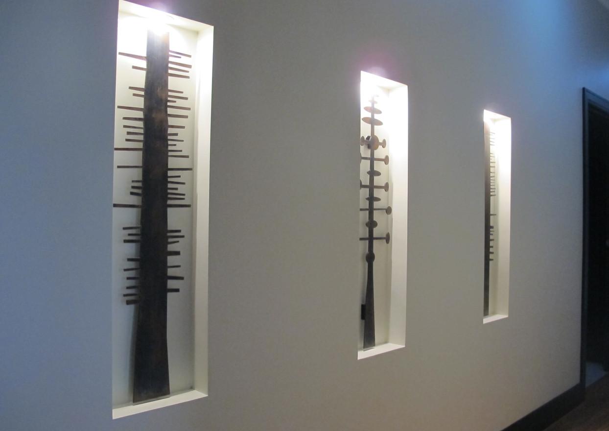 Metal art mounted in spotlit niches.