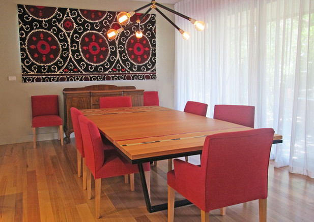 Dining room with custom  pendant light and table inlaid with strips of reclaimed road signage. An Uzbek Suzani made into a Roman blind completes the look.