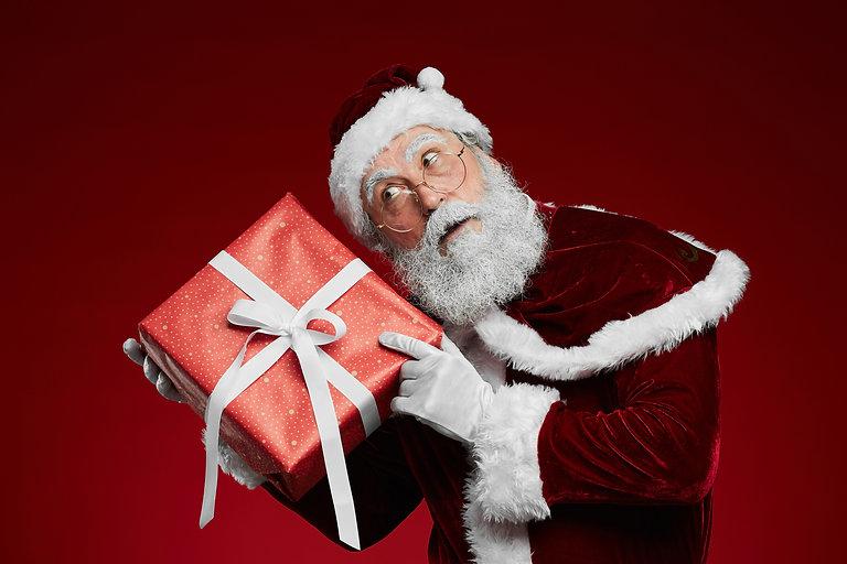 Waist up portrait of classic Santa holdi