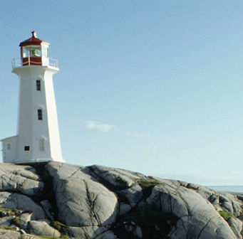 Photograph of a white lighthouse on gray rocks on a sunny day