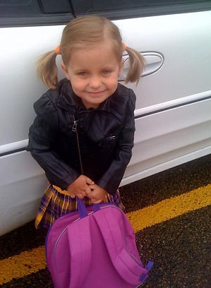 An image of Melody's daughter, Shae, when she was young. She's holding a pink backpack and smiling at the camera