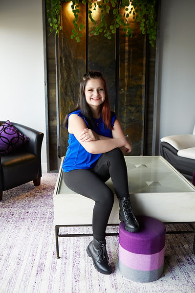 Shaelyn is sat at the front of the office on a coffee table. One of her boots is resting on a purple circular cushion.