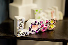 """A clay sculpture of the word """"Love"""" has pink and purple polygons colored inside the letters."""
