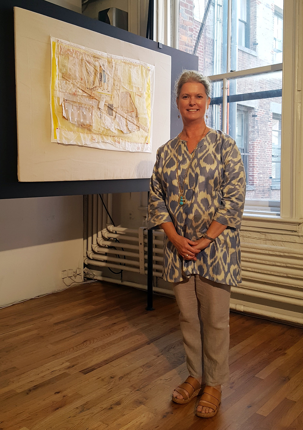 """Lily Zane stand's in front of her piece """"Measure Twice, Cut Once""""."""