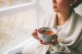 a-young-woman-drinking-tea-and-looking-o