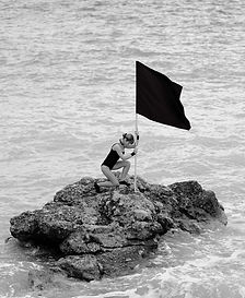woman-on-rock-formation-holding-a-flag-1
