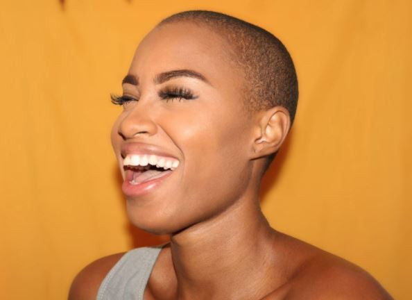 Beautiful Black Woman smiling and laughing in front of a tangerine background.