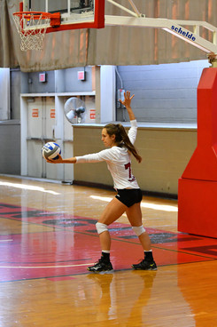 Image of a girl volleyball player serving the ball to the other team during a game - wearing long sleeve volleyball shirts with names and numbers on the backs and school logo on the fronts - miami promo shirts - Volleyball Uniforms