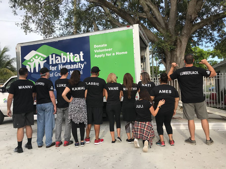 Image of a group of volunteers working with Habitat for Humanity - Volunteers wearing black t-shirts with company logos on the front and their personal names on the backs - miami promo shirts