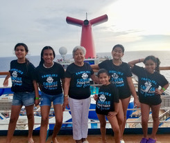 Image of a family group on a cruise ship all wearing their family cruise t-shirts which they made just for this trip