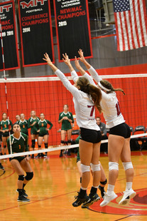 Image of 2 girl volleyball players going up for a block during a game - wearing long sleeve volleyball shirts with names and numbers on the backs and school logo on the fronts - miami promo shirts - Volleyball Uniforms