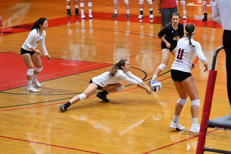 Image of a girl volleyball player diving to save a spike from the other team during a game - wearing long sleeve volleyball shirts with names and numbers on the backs and school logo on the fronts - miami promo shirts - Volleyball Uniforms