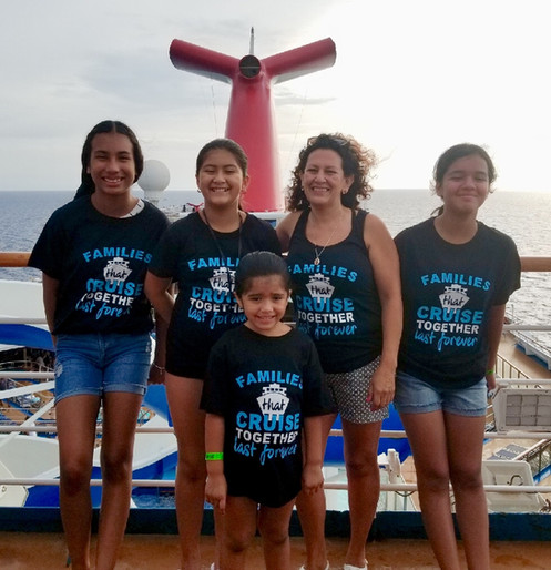 Image of a family on the top of a cruise ship all wearing their family cruise t-shirts which they made just for this trip