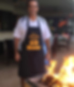 printed apron while roasting a pig in a cajaLink to the Accessories page - Image of a man wearing a custom screen  china - miami promo shirts -  Custom Printed Accessories