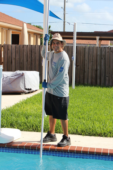 Image of a pool guy brushing a swimming pools while wearing his long sleeve heather grey t-shirts with his company logo on the back and the left chest