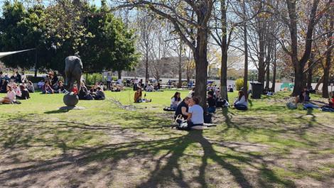 Em frente à Praça de Alimentação. Abriu o sol, os alunos aproveitam o gramado.