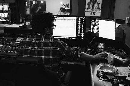 From behind Shane Salk working on two computer screens in a sound studio