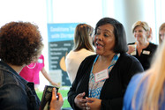 Expo exhibitor discusses program with attendee