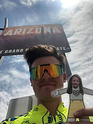 Conner holding Flat Morgan (paper cutout girl) in front if a welcome sign for the state of Arizona