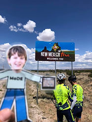Paper cutout boy (Flat Elliot) in front of New Mexico state sign; two bike riders are looking at sign