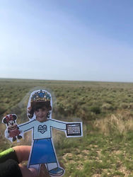 Flat MoDE girl with a princess hat and Minnie Mouse doll in front of a desert field