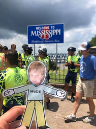 Flat MoDE Boy in front of Welcome to Mississippi sign