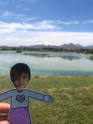 Flat Amelia being held up in front of a lake with mountains at the far distance