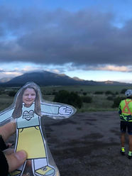 Paper cutout girl in front of mountain and desert