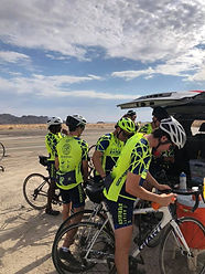 Bikers in yellow shirts preparing their bikes to ride; flat desert and large blue sky background