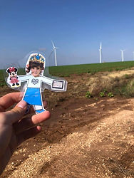 Flat paper girl being held up in front of a grassy field with windmills in the distance