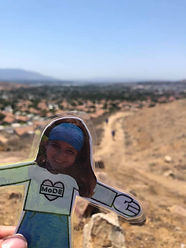 Flat Eliza (paper girl cutout) in front of a desert area
