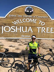"""Conner holding Flat Will (paper boy cutout) in front of a sign that says """"Welcome to Joshua Tree"""""""