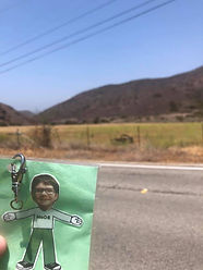 Flat Nathan (cut-out boy) held up in front of a road with a mountain in the background