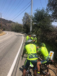 Bikers in bright yellow shirts resting before riding up a hill
