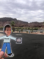Flat Logan (paper boy cutout) in front of a road with rocky mountains and palm trees in background