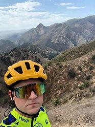 Biker in yellow helmet and shirt in fround of a huge mountain range