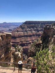 Two people admiring the view of a huge canyon