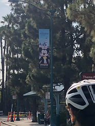 Biker about to pass a Disneyland sign