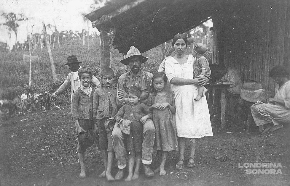 Família de pai, mãe e cinco crianças. Pai sentado ao centro com criança em pé entre suas pernas. Duas crianças em pé a sua esquerda e uma a sua direita. Na direita da foto, mãe de pé com bebê no colo. Ao fundo da foto, casa de madeira e pessoas exercendo algum ofício.