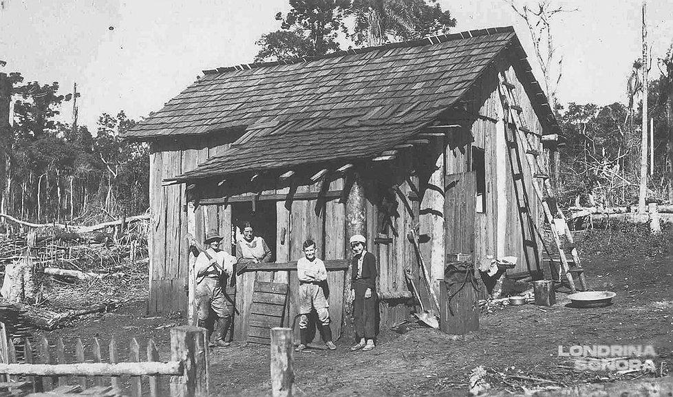 Casa de madeira com um homem e dois garotos no exterior e uma mulher dentro da casa debruçada na janela.