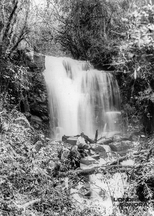 Homem sentado em pedra na frente de uma cachoeira rodeada por vegetações.