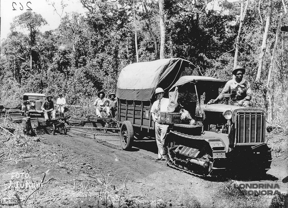 Um pequeno caminhão puxando carroças. Uma pessoa de chapéu branco escostada no caminhão. Uma em cima e algumas pessoas nas carroças atrás.