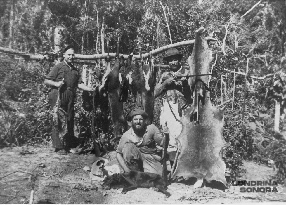 Pedaço de madeira com várias peles de animais dependuradas. Homem agachado com espingarda na mão e dois cachorros. Em pé, a esquerda, um homem sorrindo e a direita outro homem apontando a arma quase em direção à foto.