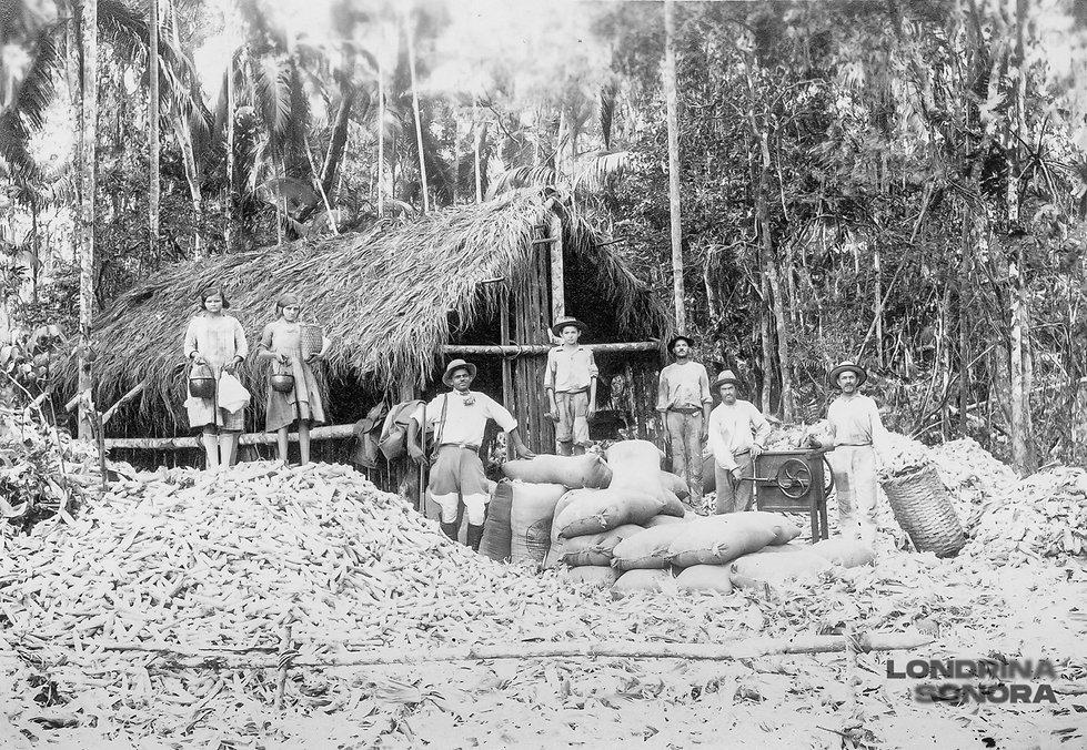 Família. Pai, mãe e cinco crianças posando em frente a uma casa, com vários sacos de grãos.