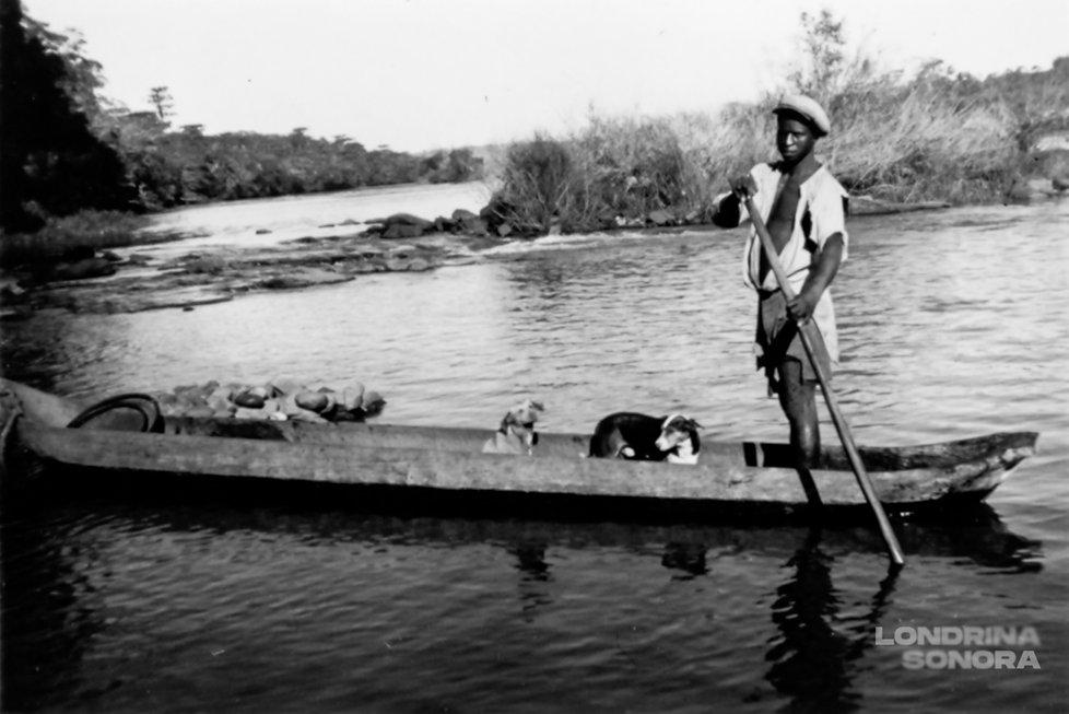 Homem segurando um remo e dois cachorros. Todos em cima de uma canoa na água.